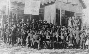 """Venäläiset sotilaat viettivät vuonna 1917 vappua yhdessä suomalaisten työläisten kanssa. Tämä vappuryhmäkuva on Savitaipaleelta. Kuva on otettu Hyrkkälän kylän työväentalon eli """"Pomppalan"""" edessä. Kansan Arkisto."""