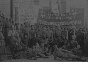 Venäläisiä sotilaita ja suomalaisia mahdollisesti Kajaanissa vuonna 1917. Vallankumouksen jälkeisissä tunnelmissa vapauden ajatus korostui lipuissa ja banderolleissa. Kuva: Työväen Arkisto.